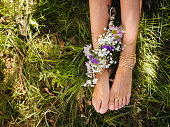 Girl's bejewelled feet in green grass with flowers