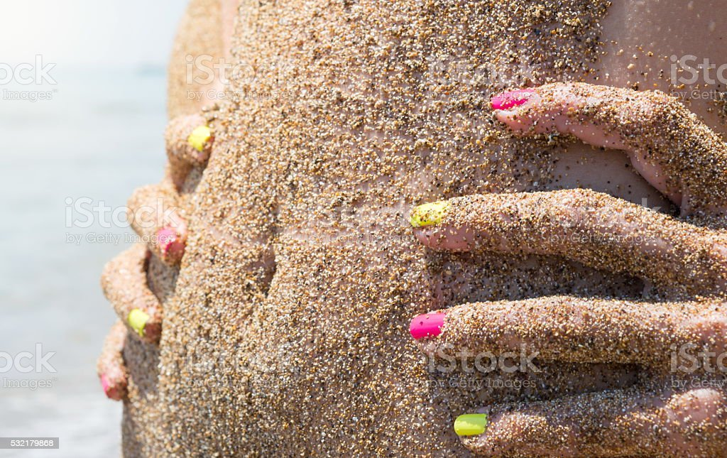 Girls belly covered with beach sand at the summer vacation