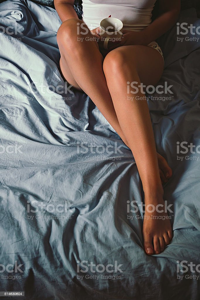 Girls body holding a cup of coffee on the bed stock photo