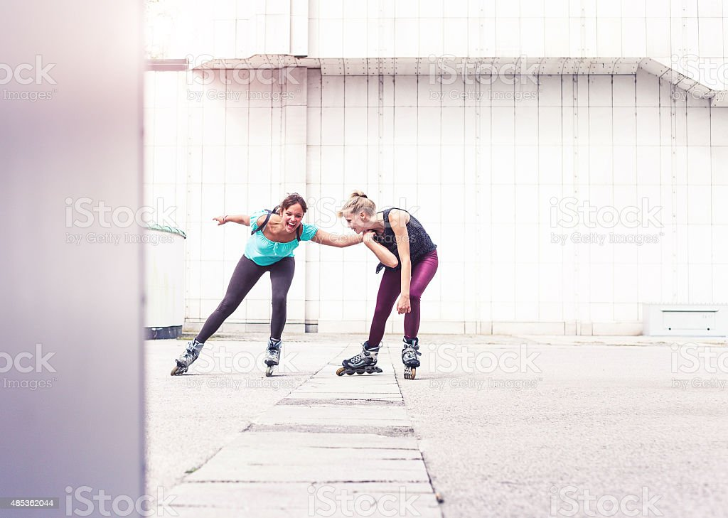 Girls bonding together and having fun with rollerskates stock photo