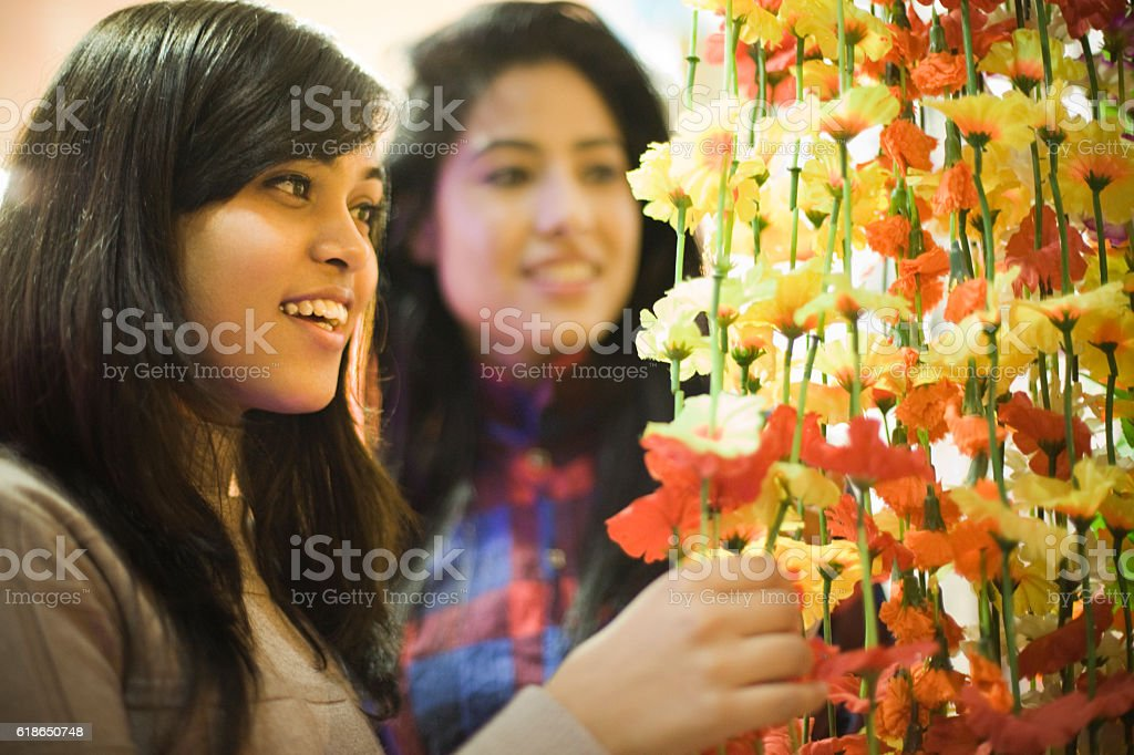Girls buying floral wall hanging in decor shop before festival. stock photo