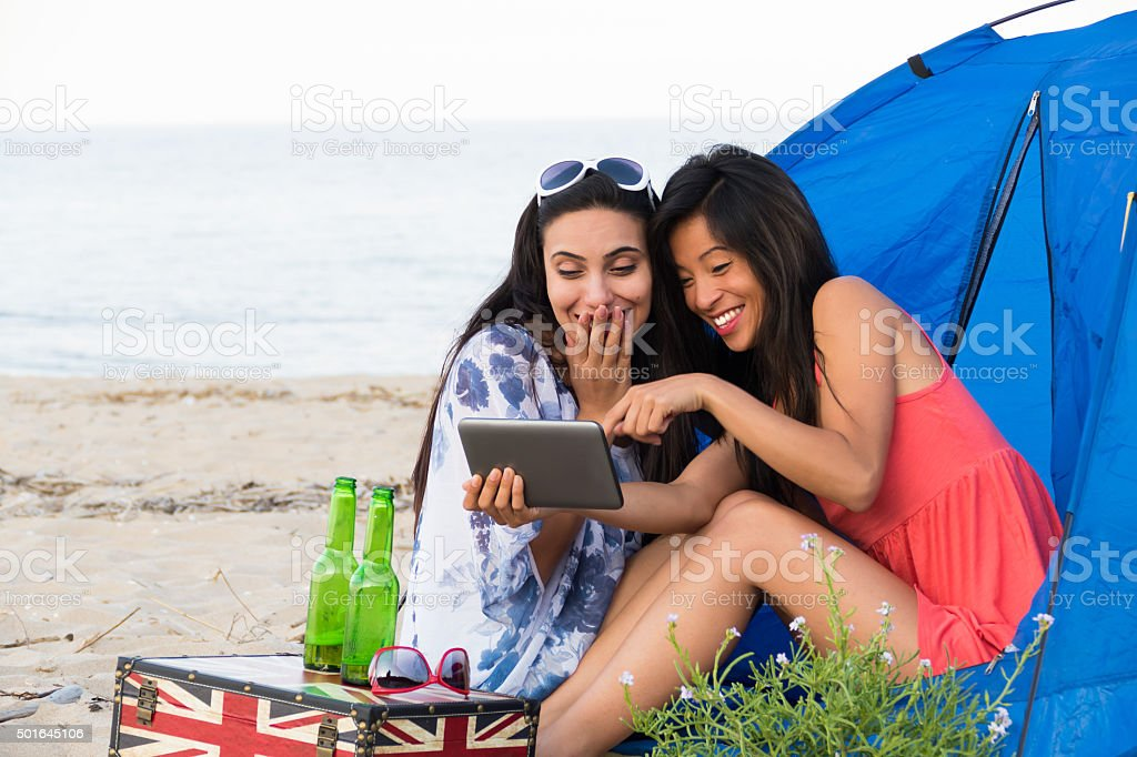 Girls camping on beach making selfie stock photo