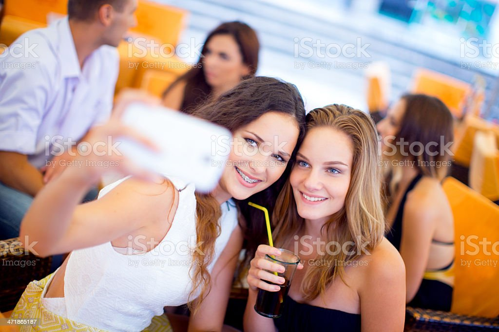 Girls capturing an image with a smart phone royalty-free stock photo