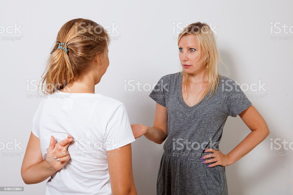 Girl's cheating her mother and crossed fingers behind his back. stock photo
