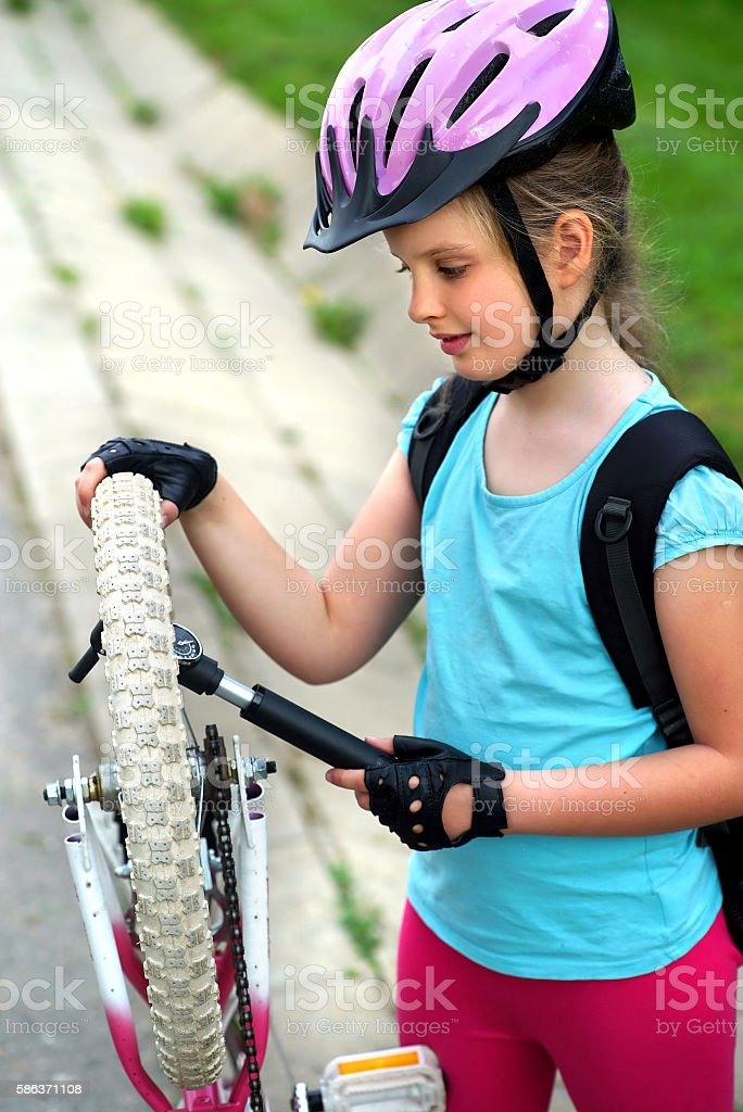 Girls child cycling pump up bicycle tire. stock photo