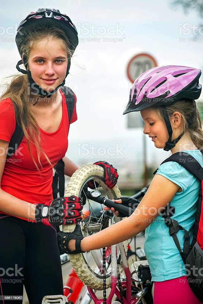 Girls children cycling Family pump up bicycle tire. stock photo