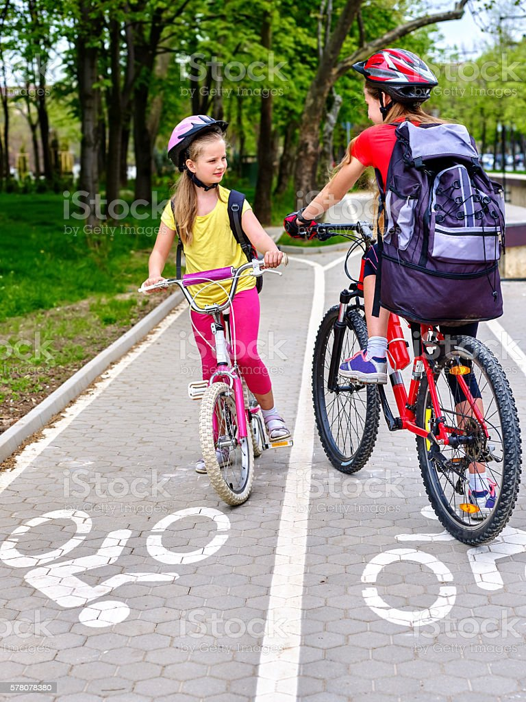 Girls children cycling on yellow bike lane. stock photo