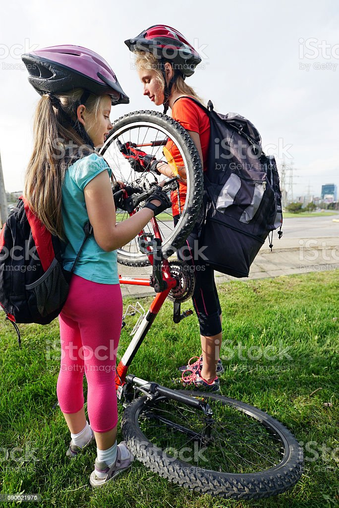 Girls children cycling pump up bicycle tire. stock photo