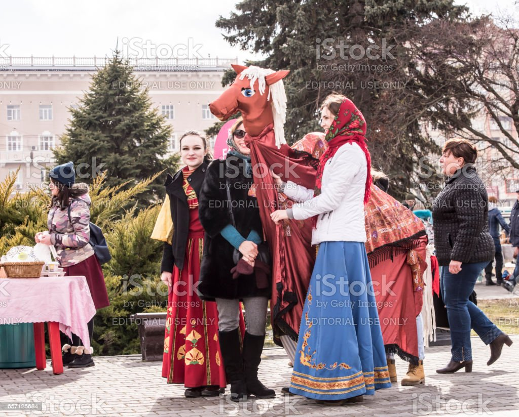 Girls dance with a decorative horse in the park for the carnival stock photo