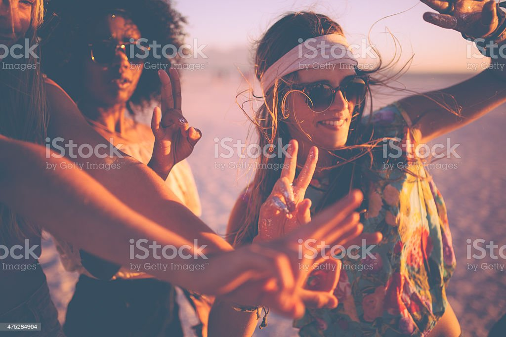Girls dancing at a beachparty at sunset stock photo