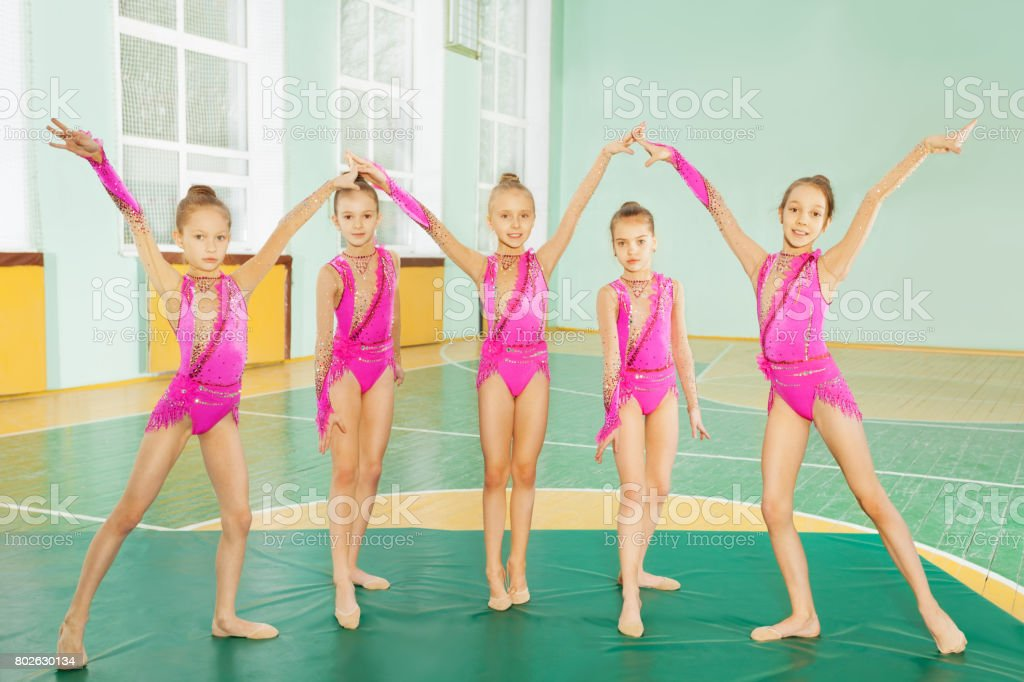 Group of 11-12 years old girls wearing pink leotards, practicing...