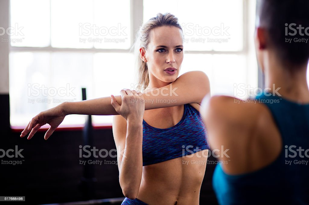 Girls doing stretching exercises after a workout at gym stock photo