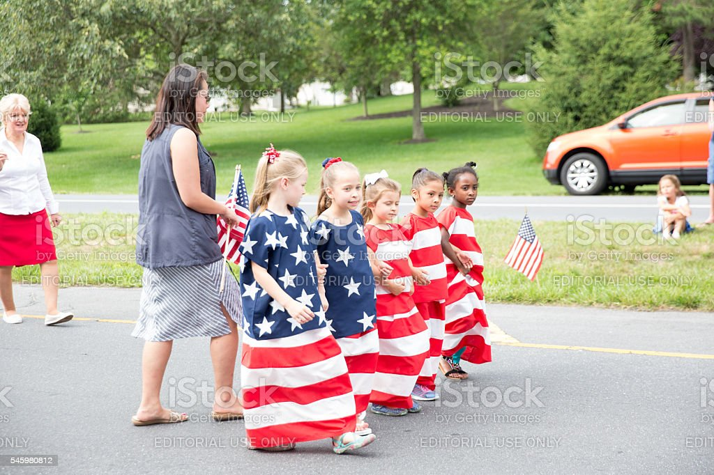 Girls dressed as American flag march in July 4th parade stock photo