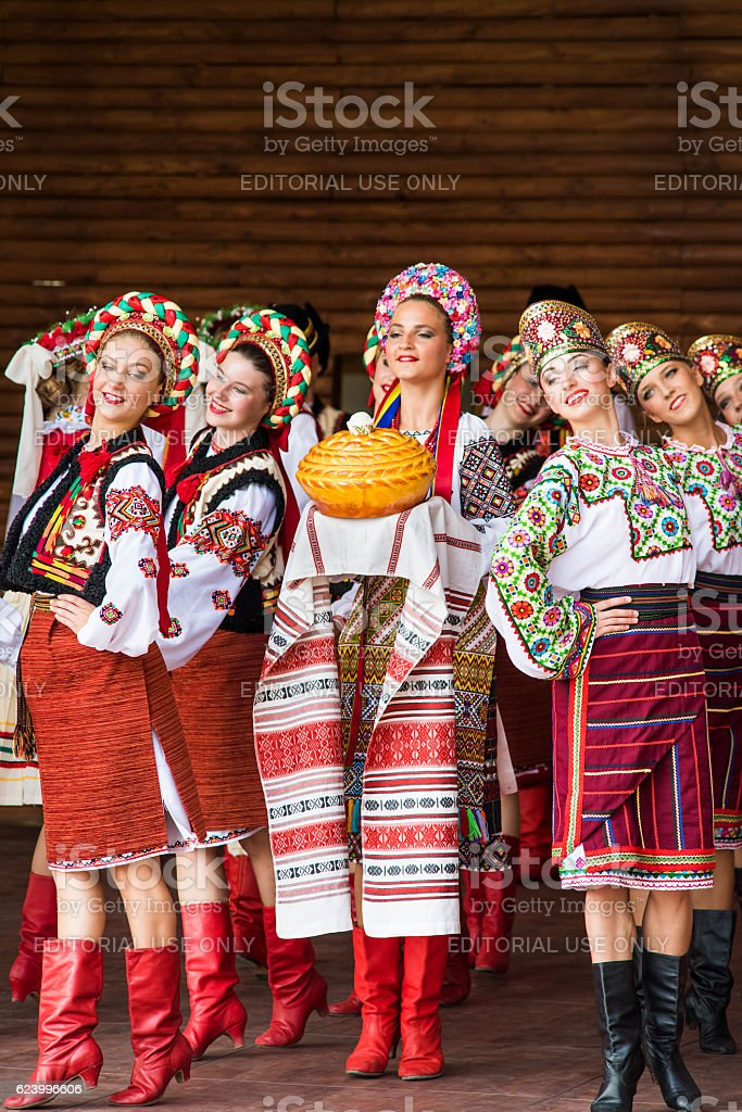 Girls dressed in traditional red Ukrainian embroidered clothes with bread stock photo