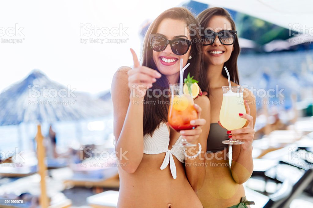 Girls drinking cocktails on beach stock photo