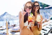 Girls drinking cocktails on beach
