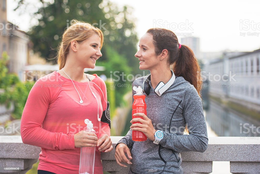 Girls drinking isotonic drinks after workout stock photo