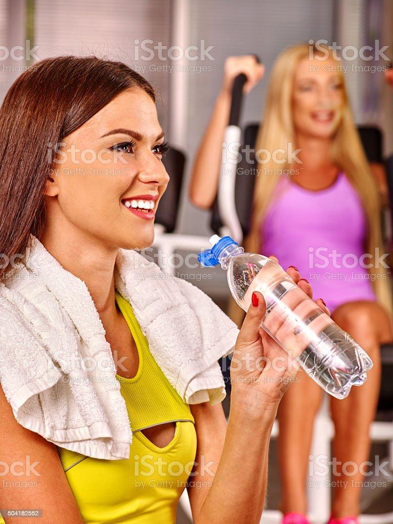 Girls drinking water in sport gym stock photo