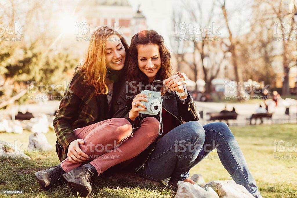 Girls enjoying instant photos stock photo