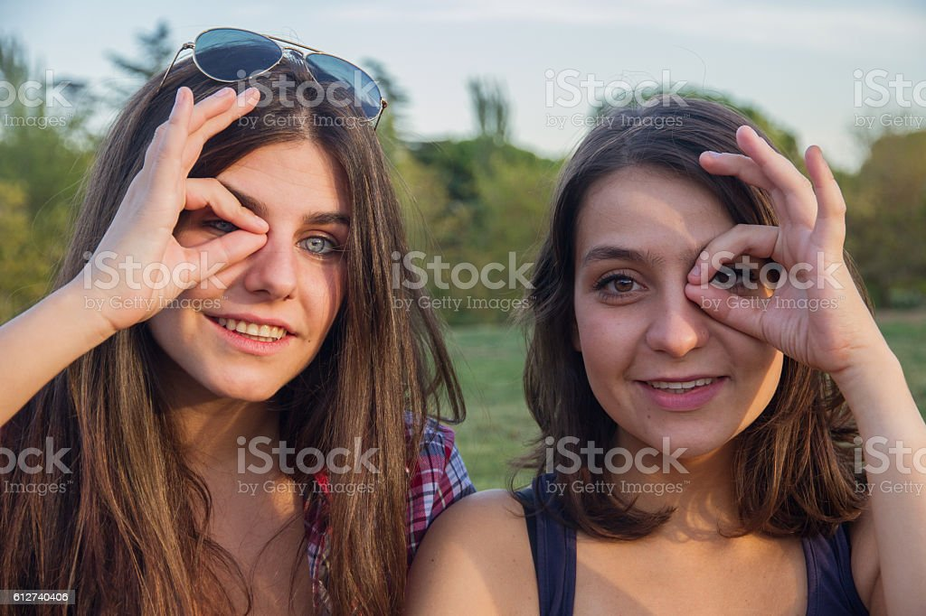 Girls enjoying while making silly in the park. stock photo