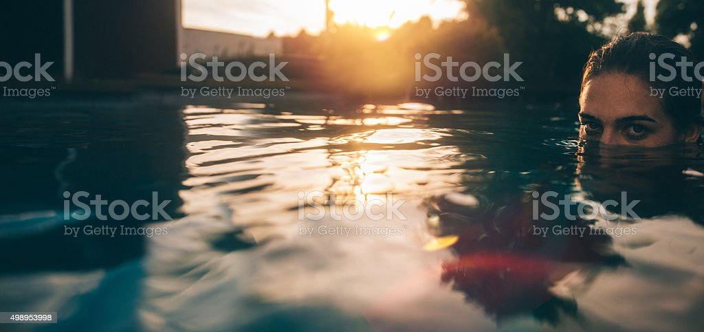 Girl's face half submerged in a late evening swimming pool stock photo