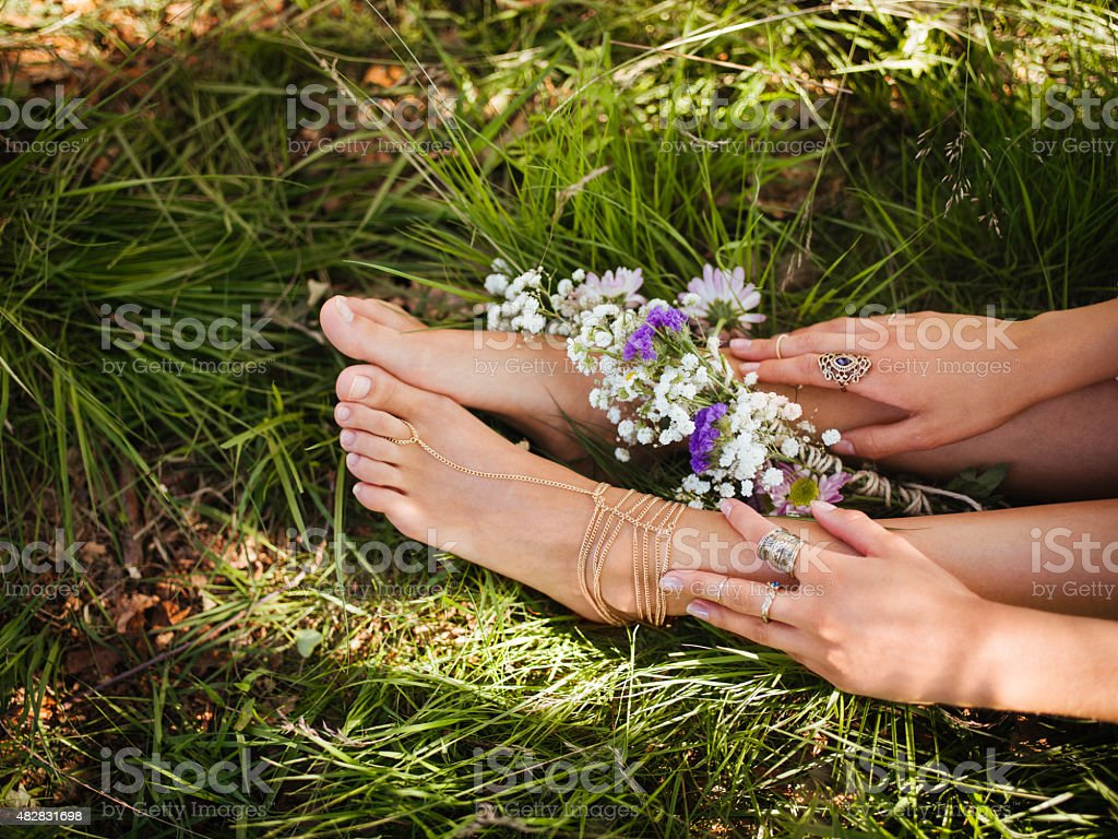 Girl's feet in grass with fresh flowers and gold jewellery stock photo