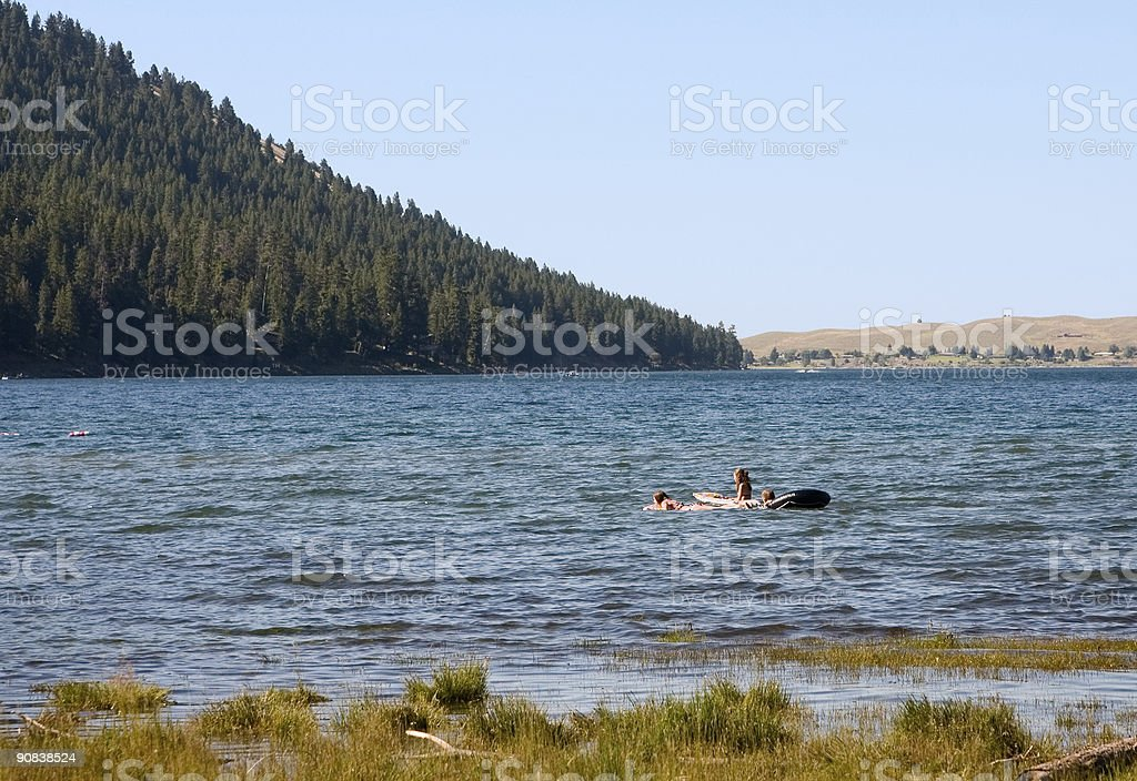 Girls floating on a forest lake royalty-free stock photo