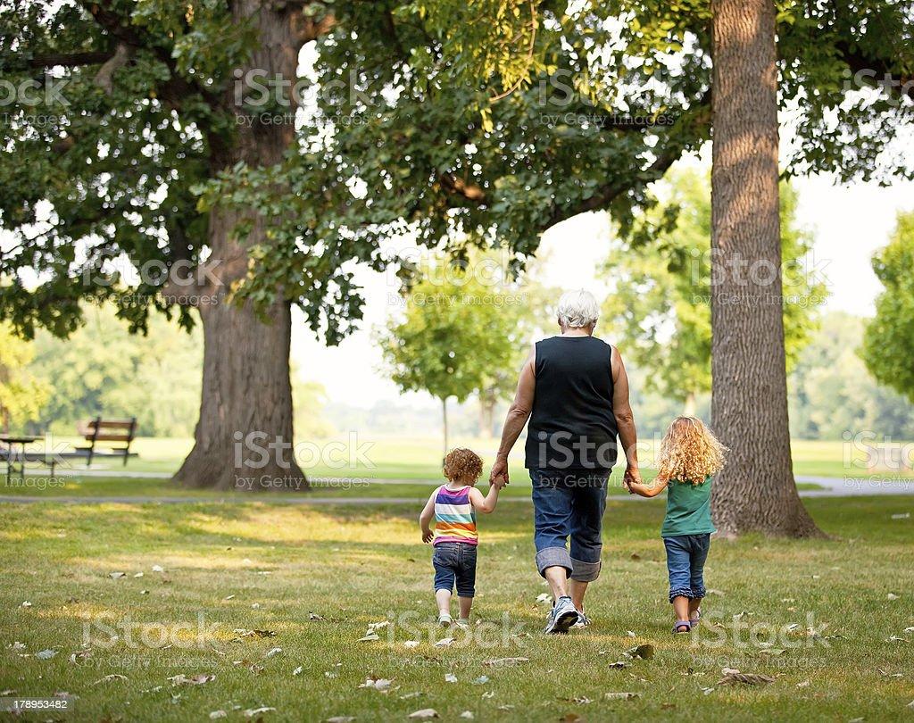 Girls & Grandma Walking in Park royalty-free stock photo