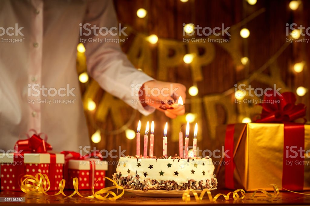 Girl's hands are lit with a candle match on the birthday cake stock photo