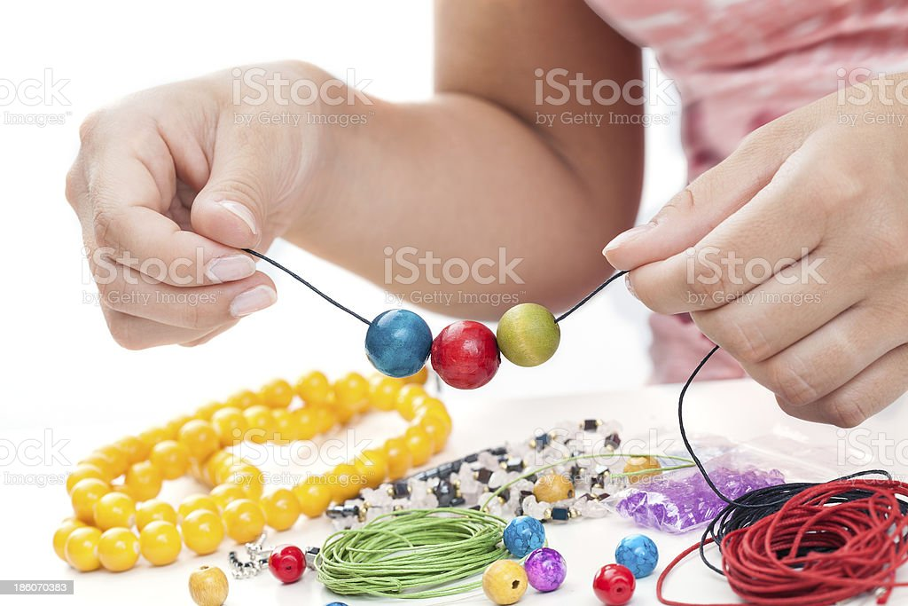 Girl's hands beading necklace stock photo