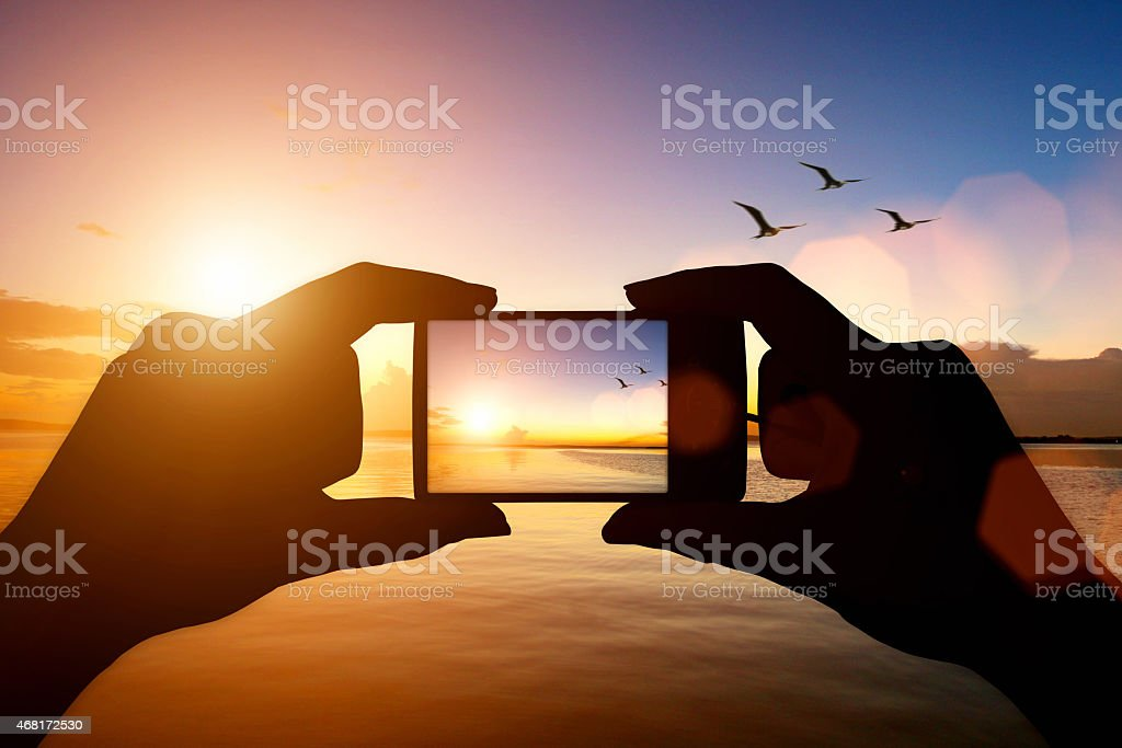 Girl's hands holding camera taking pictures of beautiful sunset stock photo