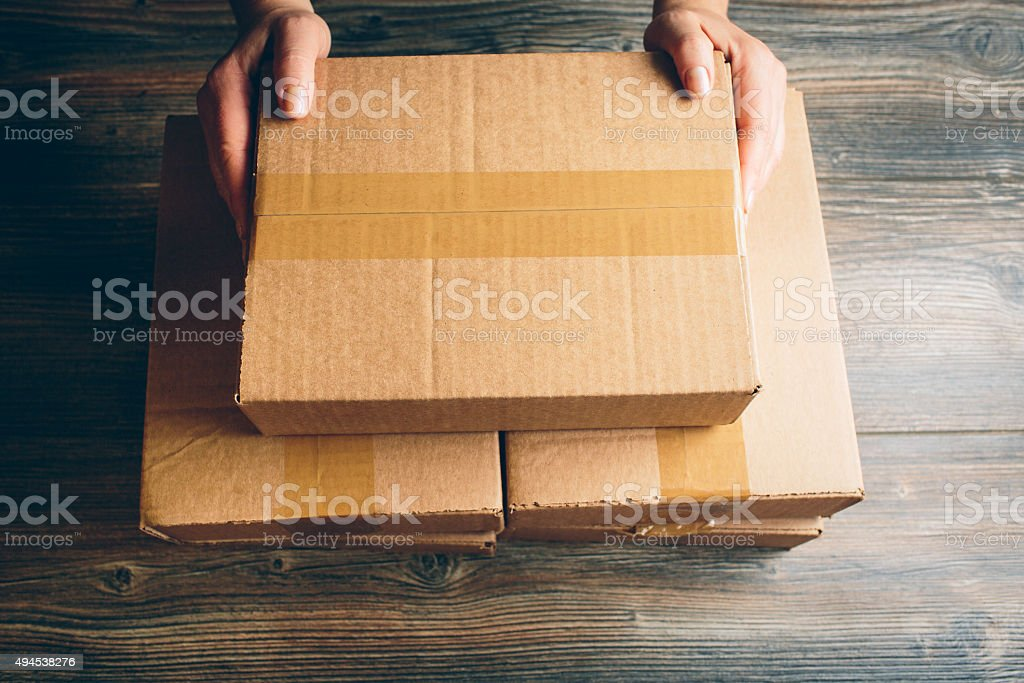 Girl's hands holding the package on the table. stock photo