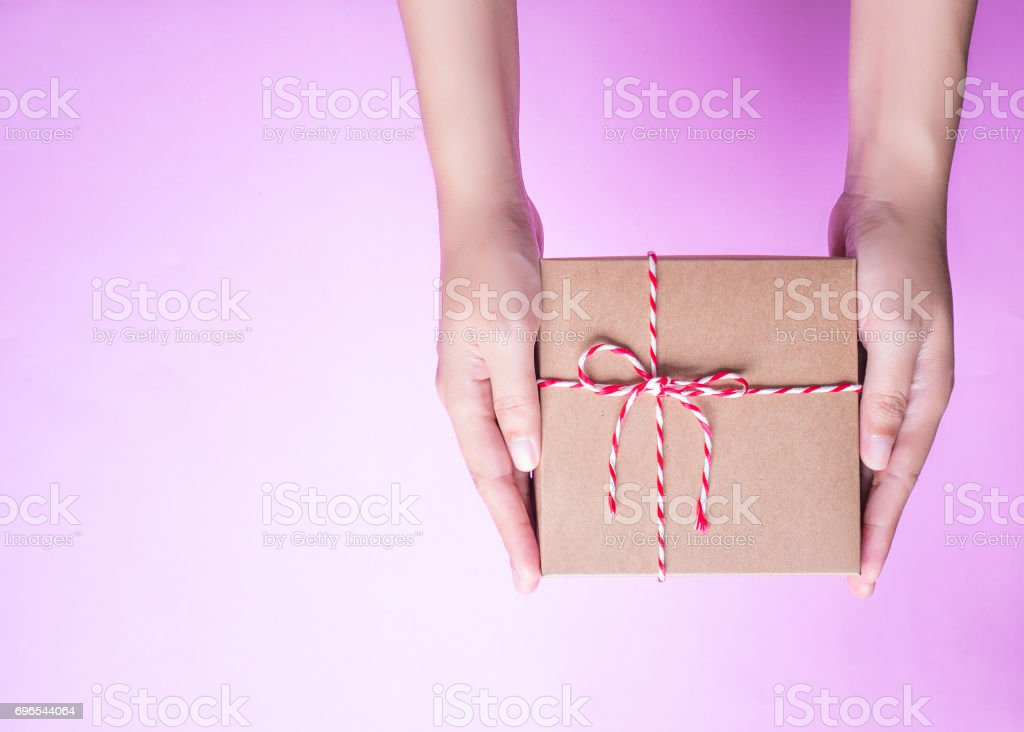 Girl's hands holding the simply package box as a present for Christmas, new year, valentine day or anniversary on pink background, top view stock photo