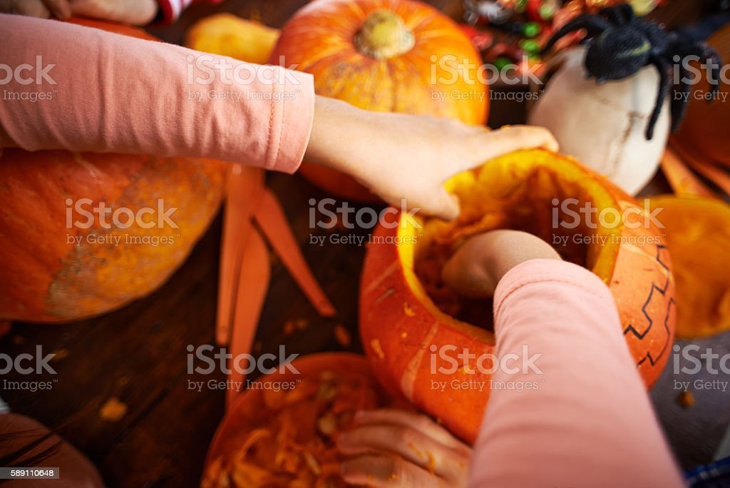 Girl's hands removing pulp from pumpkin stock photo