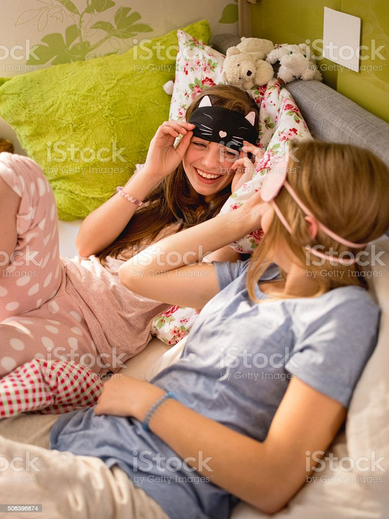 Girls having a slumber party with cute sleeping masks stock photo