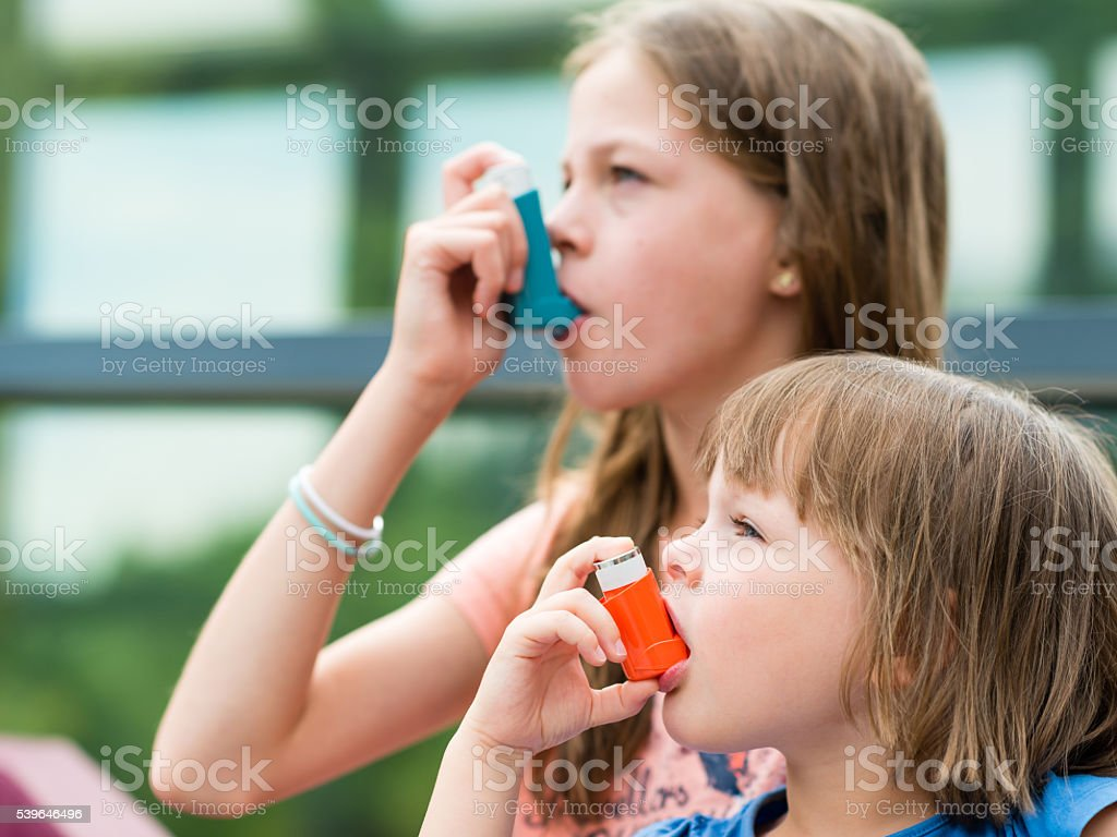 Girls having asthma using asthma inhaler for being healthy stock photo