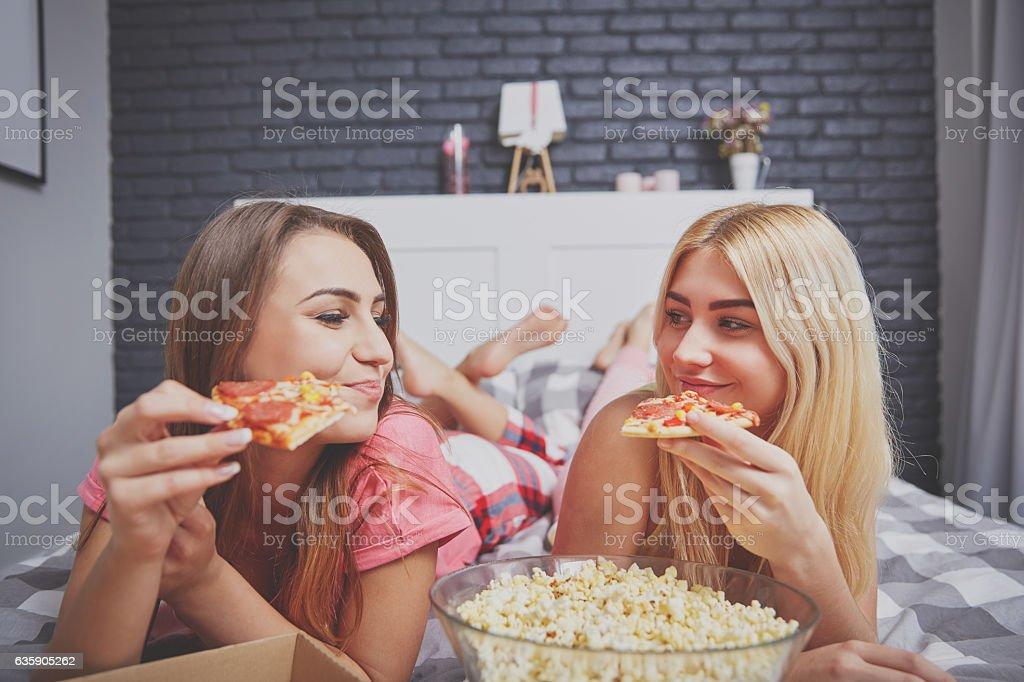 Girls having dinner in bed stock photo