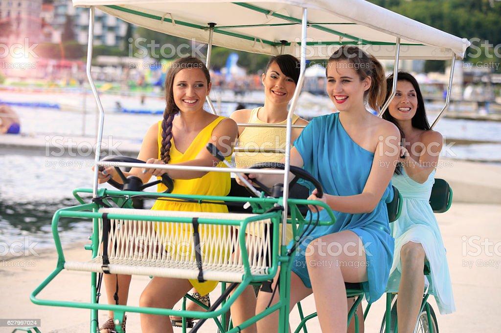 Girls having fun on surrey pedal bike at seaside stock photo