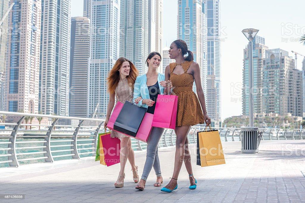 Girls having fun together shopping. Beautiful girl in dress hold stock photo