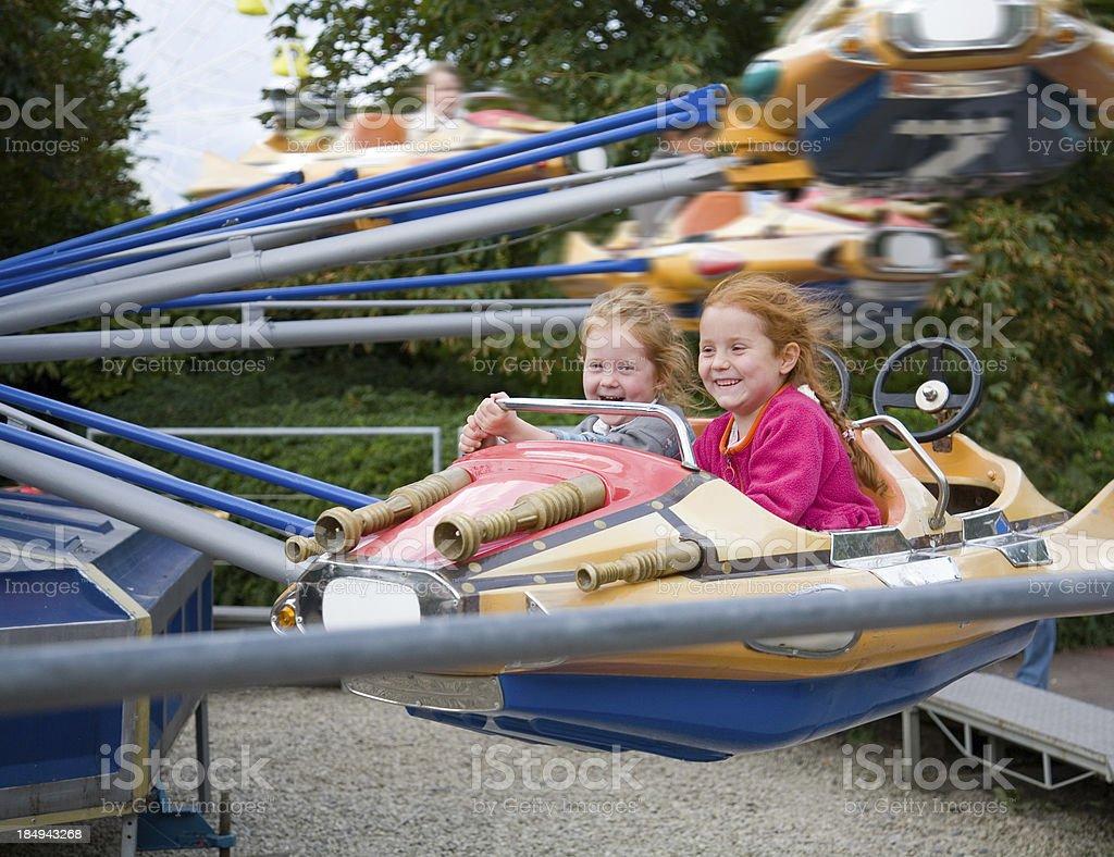 girls having joy ride on a fairground plane royalty-free stock photo
