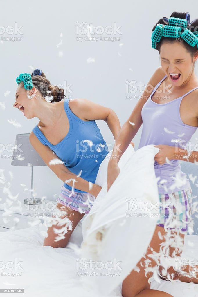 Girls having pillow fight stock photo