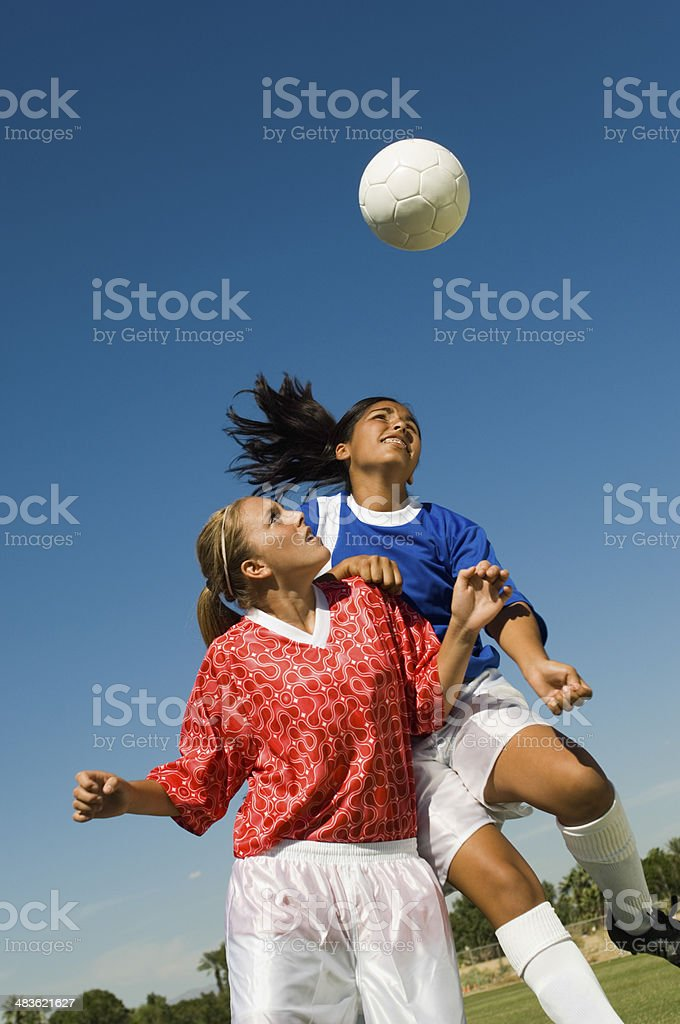Girls Heading Soccer Ball During Match stock photo