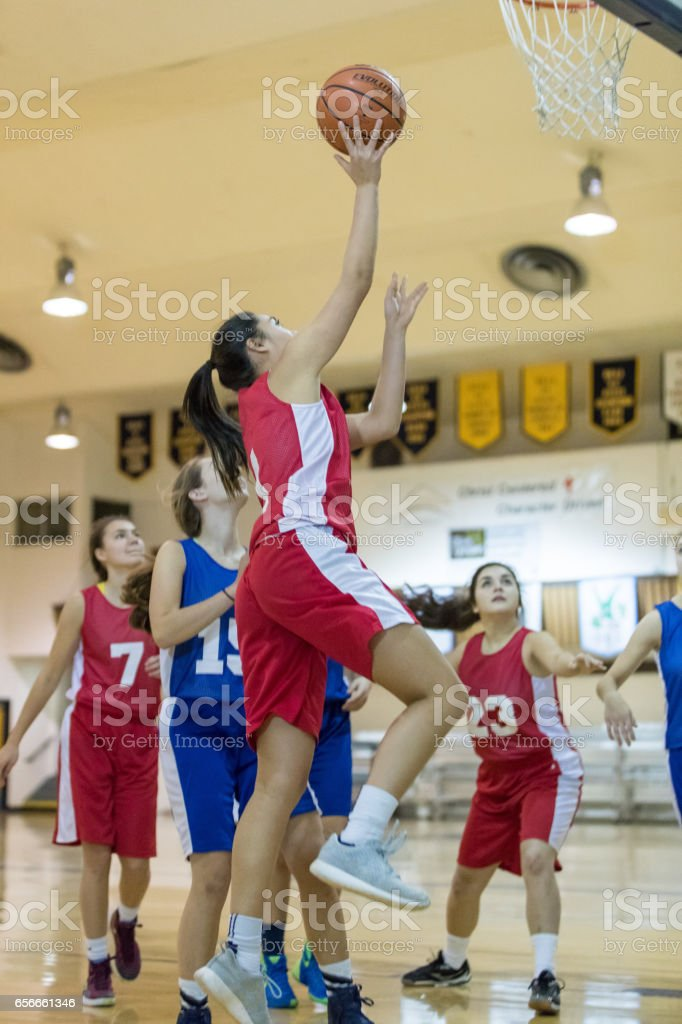 Player soars through the air to score as other players watch in the...