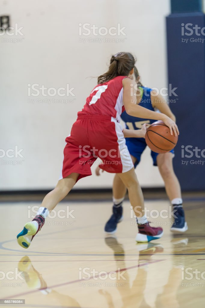 Girl dribbles at top of key and tries to drive past defender to hoop