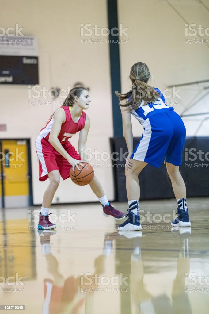 Player holds ball at top of key while defender guards her