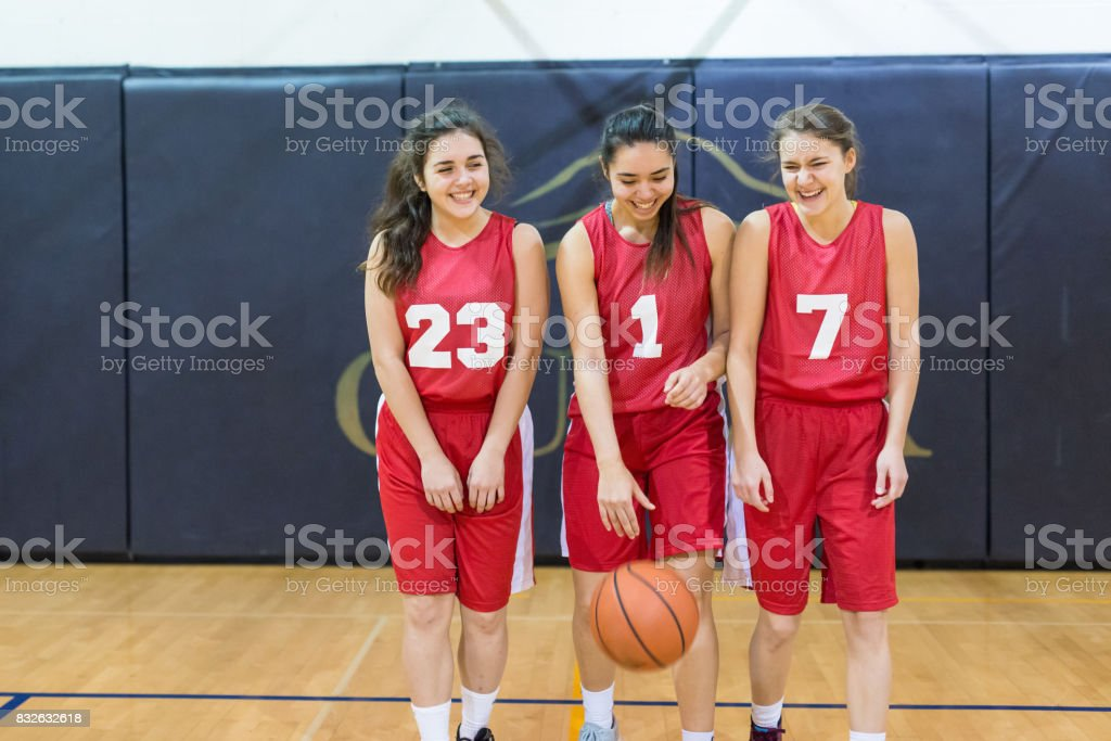 trio of girls posing with ball. They are all laughing.