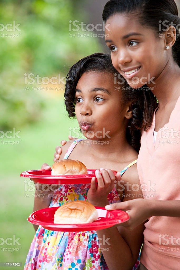 Girls holding plates with hamburger buns royalty-free stock photo