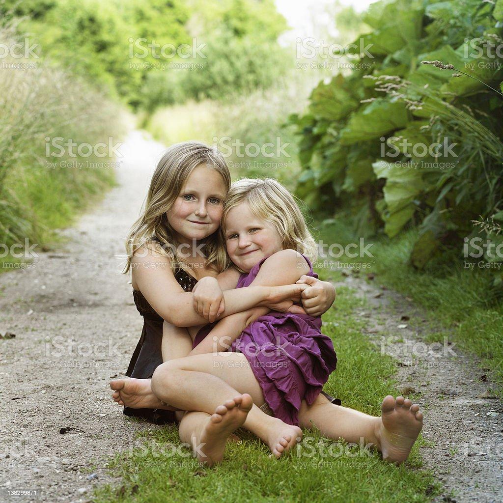 Girls hugging on dirt path stock photo