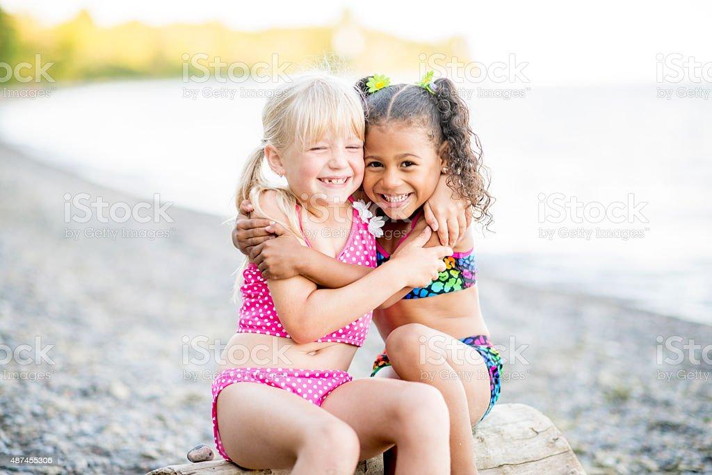 Girls Hugging on the Beach stock photo