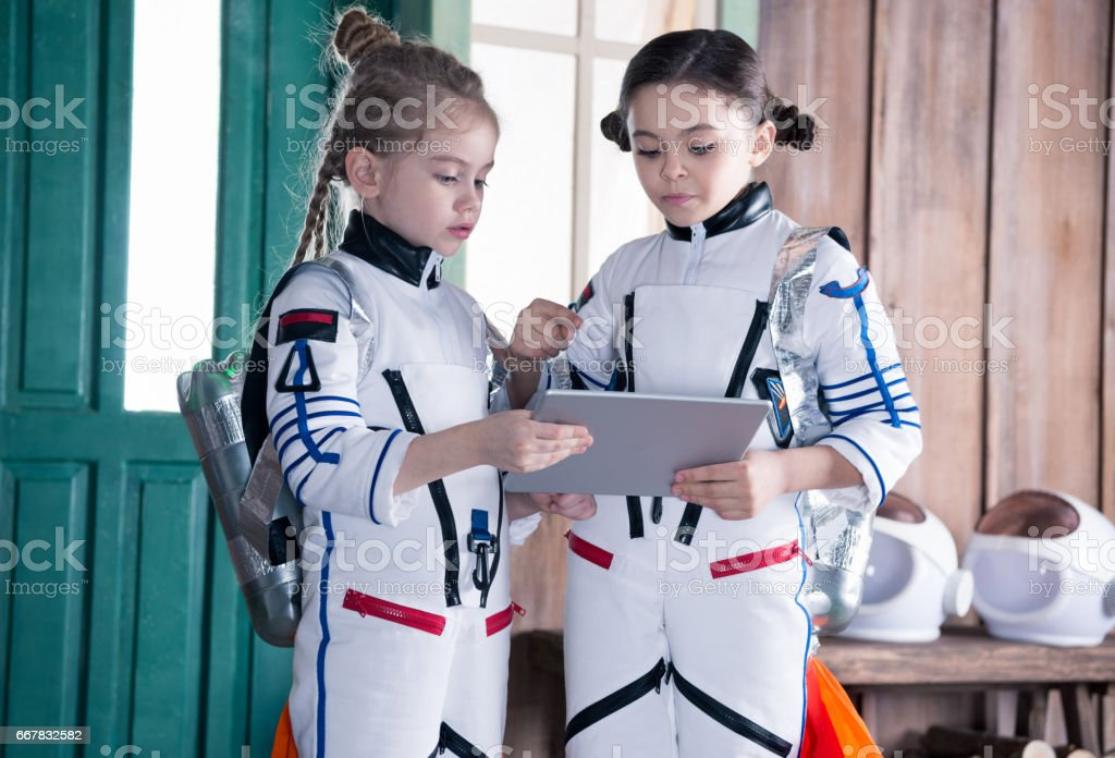 girls in astronaut costumes with jetpacks using digital tablet stock photo